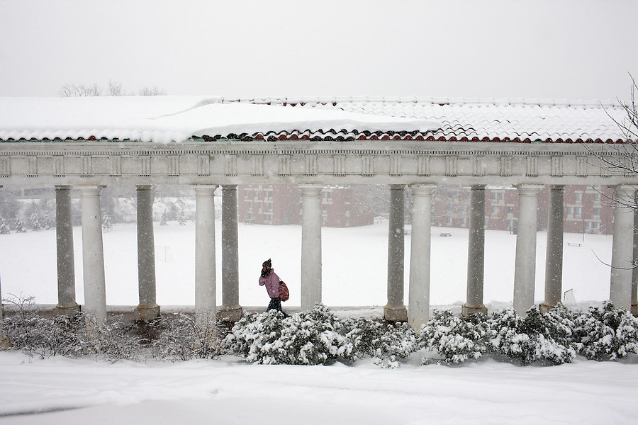 A student walks through snow Lambeth Field at the University of Virgnia,