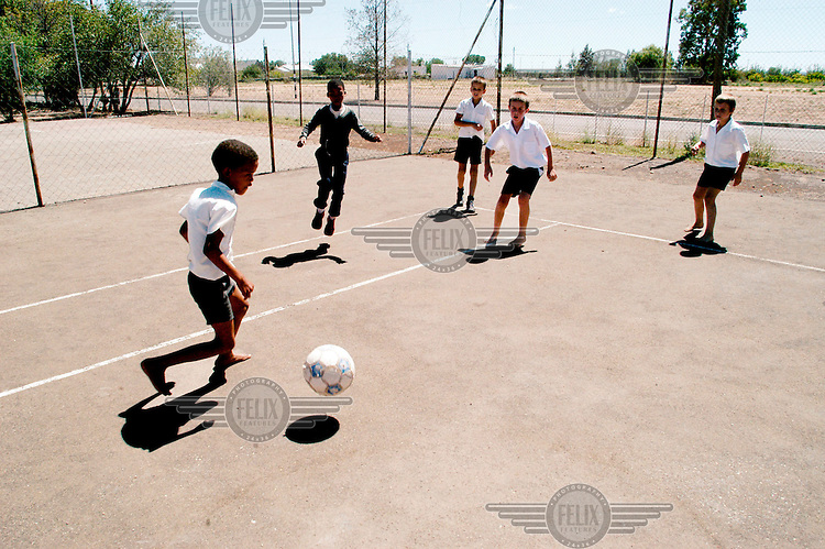 Kids play football together during a school break.