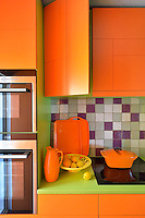 Bright orange kitchen cabinets chime with lime green work surfaces in this retro-style kitchen