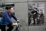 Nov 10, 2009 - Tokyo, Japan - A Japanese woman rides past large pictures depicting the collapse of the Berlin Wall along the wall of the German Embassy in Tokyo.