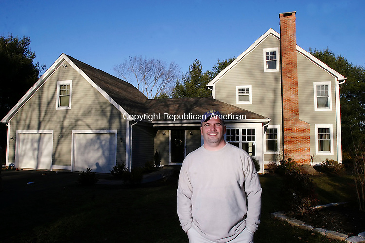 SOUTHBURY, CT, 03/27/07- 032807BZ08- Louis Costabile poses in front of his Southbury home Wednesday afternoon. His original house on this property was destroyed by fire caused by the spontaneous combustion of oily rags left in a bucket on his breezeway.<br /> Jamison C. Bazinet Republican-American