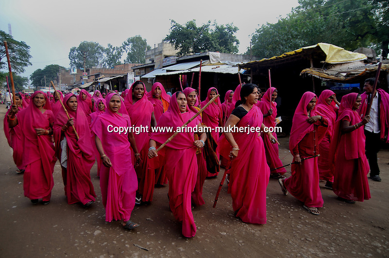 Gulabi Gang during a rally lead by Sampat Pal Devi against a Government official, in a town near Fatehpur in Uttar Pradesh. Sampat pal Devi the commander of Gulabi Gang fights for women empowerment, justice and rights among the poor people of Bundelkhand region of Uttar Pradesh. Sampat Pal Devi comes from a poor family in Bundelkhand - the poorest region of India. The region is fraught with abject poverty, gross under development, lack of law and order, and stark casteism in which the Brahmins and other higher caste people treat their low caste brethren with disdain. Out of such situation when Sampat Pal Devi decided to speak up for the poor, she has been winning heart felt gratitude of the poor as well as enmity of the high caste people and grudging respect of the law enforcement officials who used to be largely inactive in these badlands of North India. Initially, she began with helping distressed women - victims of domestic violence and dowry system, but soon started getting other cases of nature of land dispute and under development. She emerged as a fiery leader in 2007, when she beat up the OC of the local police station while demanding release of a dalit woman kept locked up in the cell for thirteen days without being charged with a case.Today, she has a huge fan following of some 25 hundreds of thousands of women (spread across 8 districts of the state of UP) who have come to be known as Gulabi Gang or Pink Vigilante Women for their vibrant pink sarees - the costume of the gang; and fiery nature of dealing with injustice. When verbal negotiations for justice fail they resort to beating up. Sampat Devi is viewed as a messiah with the promise of bringing back law and order for the poor, in these mafia troubled areas. Today, perpetrators are simply scared of her as she does not hesitate to challenge law and order and even system - to win justice for the poor. More complaints related to domestic violence and other problems are registered now with the police than