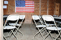 American flags hang in the barn before satirical presidential candidate Vermin Supreme delivers a stump speech at Ten Rod Farm in Rochester, New Hampshire. Supreme's platform advocates a pony-based economy, using zombies to solve the energy crisis, and other outlandish ideas. Supreme has been on the New Hampshire primary ballot in 2008 and 2012, though he has running for president in 1992. Vermin Supreme will be on the Democratic party ballot in the 2016 New Hampshire primary.