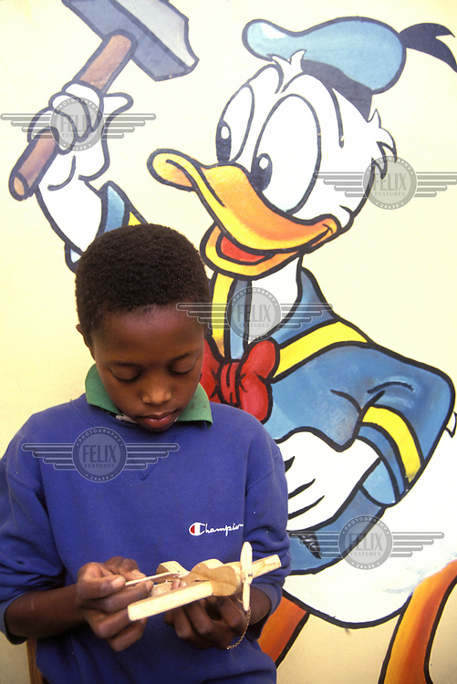 © Giacomo Pirozzi / Panos Pictures..CAPE VERDE..Boy building a model aeroplane and getting hit on the head by Donald Duck.