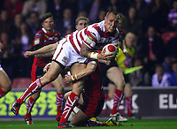 PICTURE BY VAUGHN RIDLEY/SWPIX.COM - Rugby League - Super League - Wigan Warriors v Warrington Wolves - JJB Stadium, Wigan, England - 23/03/12 - Wigan's Gareth Hock is tackled by Warrington's Brett Hodgson.