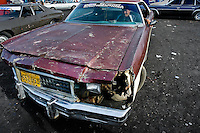 A rusty and damaged American classic car from 1970s, used as a shared taxi, waits on the stand in Maracaibo, Venezuela, 9 May 2006.