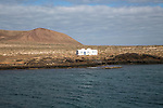 Isolated whitewashed house and Agujas Grandes volcano, La Isla Graciosa, Lanzarote, Canary Islands, Spain