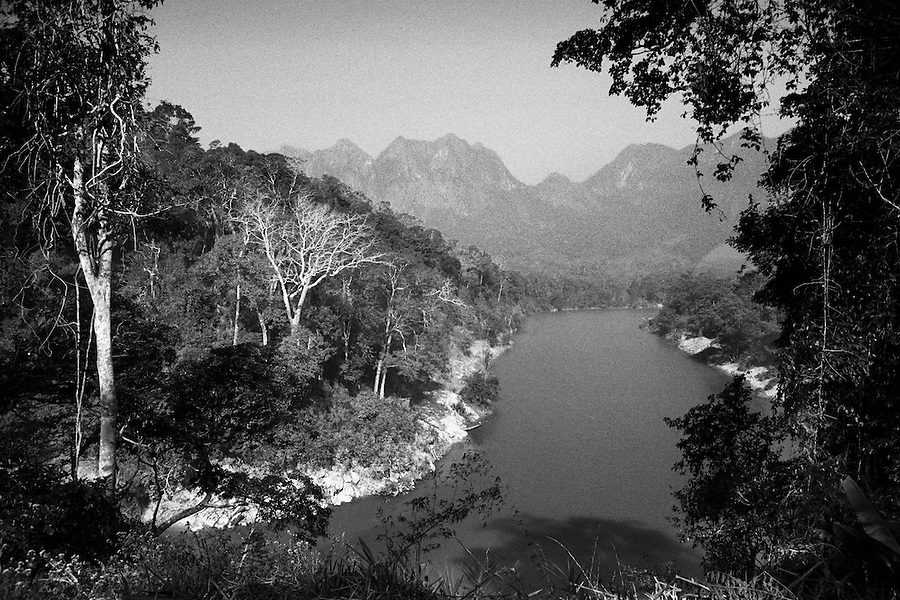 "Mekong Dam Victims - Laos. View of the Nam Gnouang River where the dam company is completing a new 70m high dam known as the Theun Hinboun Expansion Project. After the construction of the Theun-Hinboun Dam in Laos more than 29,000 people in 71 villages have lost fisheries, rice fields, vegetables gardens and fresh drinking water supplies as a result of the dam. An expansion project is currently under construction and will displace another 4,200 mostly indigenous people from their lands in the reservoir area and displace or negatively affect another 50,000 people living downstream, on project construction lands, and in resettlement host villages. Known as ""The Mother of Waters"", more than 60 million people depend on the Mekong river and its tributaries for food, fresh water, transport and other aspects of daily life. The construction of big dams is now threatening the life of these people aswell as the vital and unique ecosystem of the river."