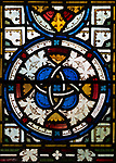 Elaborately decorated pattern of stained glass window including flowers and geometric design inside the church at Sibton, Suffolk, England, UK