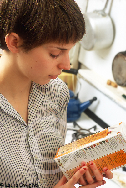 Young adult woman in kitchen food preparation reading label on packaged food
