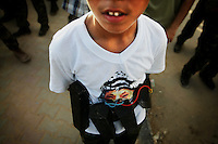 A Palestinian boy wearing a t-shirt with picture of the late President Yasser Arafat and a fake suicide bomber belt attends a gathering to celebrate the Israeli pullout from Gaza Strip in Gaza City September 1, 2005. Israel held its first public talks with Pakistan on Thursday and Jordan's king was expected to visit the Jewish state soon in signs of a thaw with the Muslim world after its evacuation of Jewish settlers from Gaza.   REUTERS/Damir Sagolj
