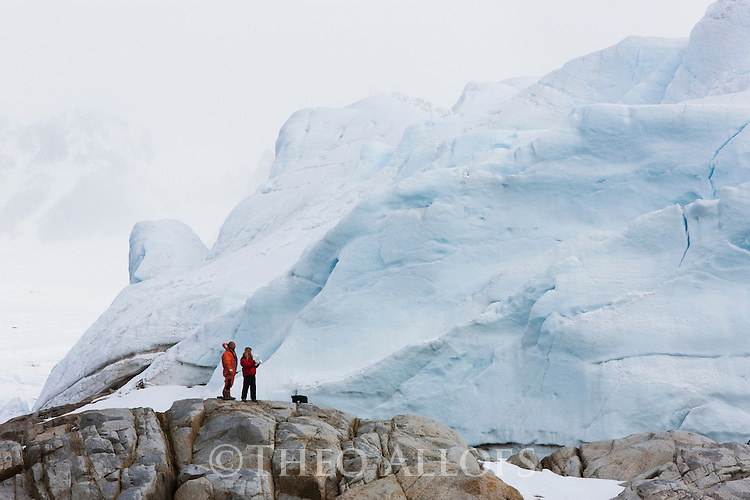 Norway, Svalbard, 2 people standing on rock in front of large glacier