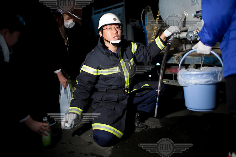 A fireman hands out water at an emergency evacuation center for victims of the recent earthquake and tsunami. On 11 March 2011 a magnitude 9 earthquake struck 130 km off the coast of Northern Japan causing a massive Tsunami that swept across the coast of Northern Honshu. The earthquake and tsunami caused extensive damage and loss of life and damaged Fukushima nuclear reactor. Two of the power station's reactors sustained extensive damage after explosions at the plant.