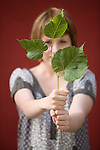 A beautiful young woman holds a branch of three leaves.