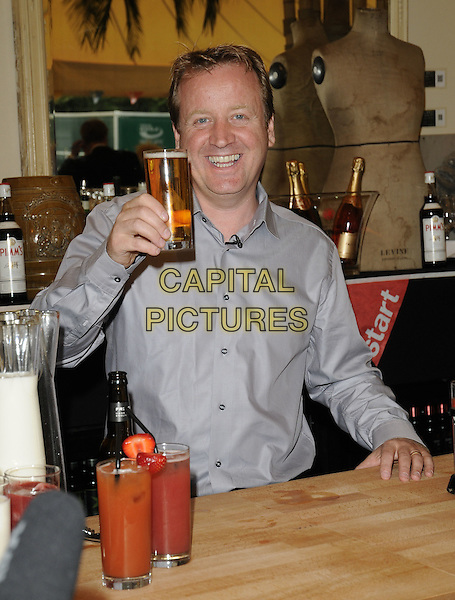 "JAMIE GRAINGER-SMITH.""Launch of The Start Sustainable Pop-Up Restaurant with Think Eat Drink"",  .Lancaster House, Stable Yard, London, UK..July 26th, 2011.half length pink jacket drink beverage beer drink grey gray shirt .CAP/CAN.©Can Nguyen/Capital Pictures."