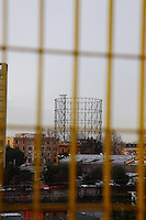 Roma, Italy, Garbatella: In a rainy day, an artistic panoramic view  panoramic view across a yellow grille, from piazza Giancarlo Vallauri towards via Ostiense, with the well known beautiful old gasometer that dominates onto the background. Digitally Improved Photo.