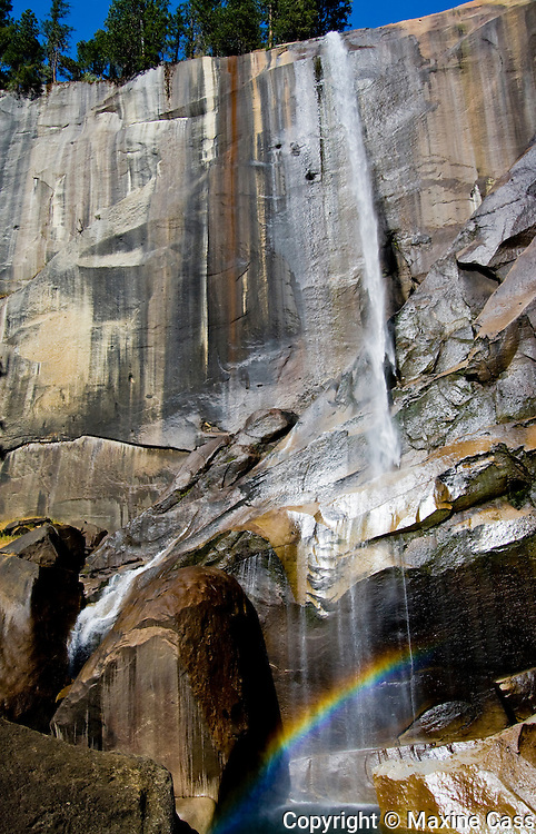 At Vernal Fall, Yosemite National Park, California, in fall/autumn, a rainbow appears above an emerald pool.  In spring and summer, the pool is obscured by the torrent of cascading Merced River water that creates the upper Mist Trail. United States of America