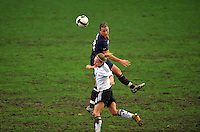 Abby Wambach heads the ball over a German opponent.  The USA captured the 2010 Algarve Cup title by defeating Germany 3-2, at Estadio Algarve on March 3, 2010.