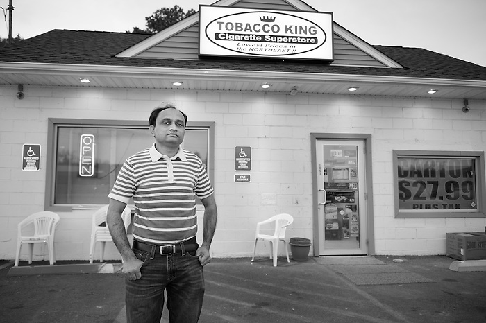 An Immigrant Indian Man standing outside of a discount cigarette store in Matamoras Pennsylvania