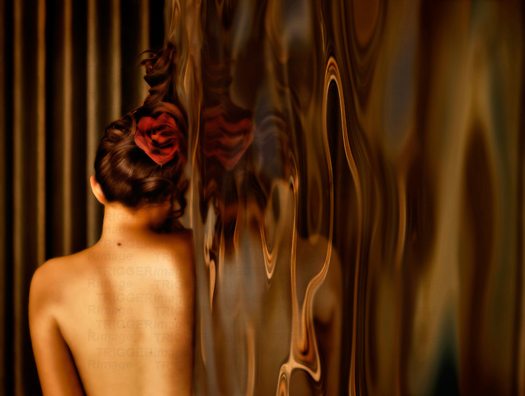 A young woman with a red rose in her hair laying on a reflective rippling surface