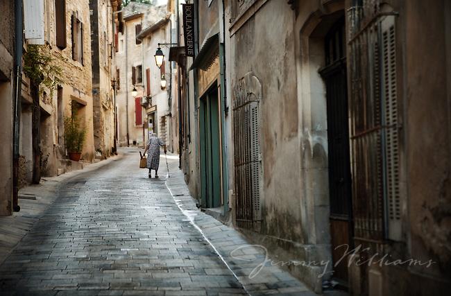 An elderly woman walks down an narrow street in Menerbes, France