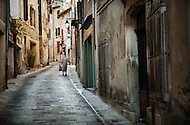 An elderly woman walks down an narrow street in Menerbes, France