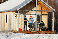 From the porch of the musher cabin, Lance Mackey, Martin Buser and Mike Williams Jr. watch Sebastian Schnuelle leave and take over first place at the ghost-town checkpoint of  Iditarod during the 2011 Iditarod race..