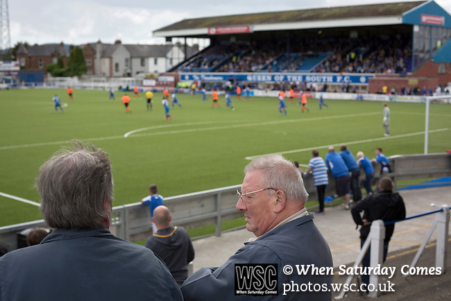 Queen of the South 2 Stranraer 0, 11/08/2015. Scottish Challenge Cup first round, Palmerston Park. A man talking to a fellow supporter in the home end during the first-half at Palmerston Park, Dumfries, as Queen of the South (in blue) host Stranraer in a Scottish Challenge Cup first round match. The game was the opening match of the season in a competition open to sides below the Scottish Premiership. Queen of the South won the match 2-0, watched by a crowd of 1229 spectators. Photo by Colin McPherson.