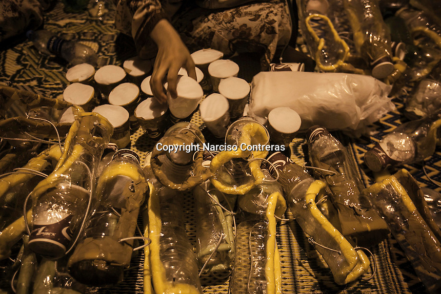 In this Thursday, Aug. 01, 2013 photo, female supporters of the ousted president Mohammed Morsi make gas masks by plastic empty bottles as they prepare themselves for an assault at the sit-in of Cairo University, in the Giza district. (Photo/Narciso Contreras).