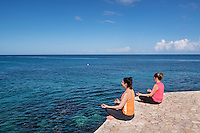 Two women practice yoga from a waterfront ledge, Negril, Jamaica.