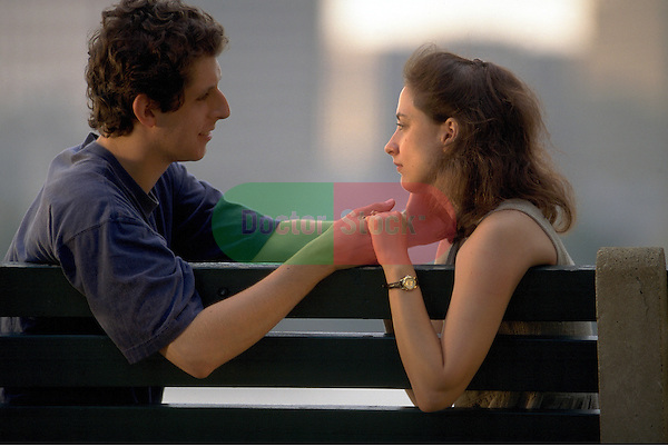 young man comforting young woman on park bench