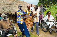 ldobson@wbhq.com 512 627-1841- Uganda- A joyous woman is delivered into a new wheelchair, by two friends helping out at a Free Wheelchair Mission distribution.