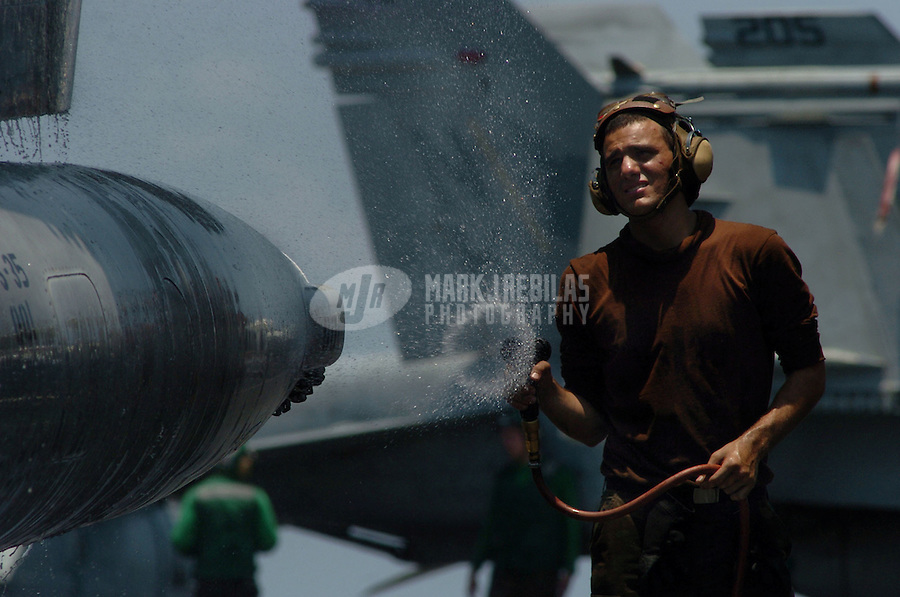 "040908-N-6213R-005 South China Sea (September 8, 2004) - Airman Daniel Hernandez sprays down an S-3B Viking from the ""Blue Wolves"" of Sea Control Squadron Three Five (VS-35) during a plane wash on the flight deck aboard USS John C. Stennis (CVN 74). Plane washes are conducted every 14 days to prevent corrosion as well as cleaning dirt and oil from parts and components. Stennis and embarked Carrier Air Wing Fourteen (CVW-14) are currently participating in a scheduled deployment to the western Pacific Ocean. Photo by Mark J. Rebilas"