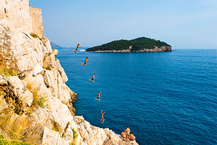Photo of cliff jumping at Buza Bar, aka Cafe Buza, Dubrovnik, Dalmatian Coast (Dalmacija), Croatia. This is a composite photo of Buza Bar (Cafe Buza), a very popular bar in Dubrovnik. It is perched on a cliff and people can regularly be seen cliff jumping from the rocks at Buza Bar (Cafe Buza) into the beautiful blue Mediterranean Sea below. Directly opposite Buza Bar (Cafe Buza) is Lokrum Island, just off the Adriatic Coast of Dubrovnik, Dalmacija, Croatia.