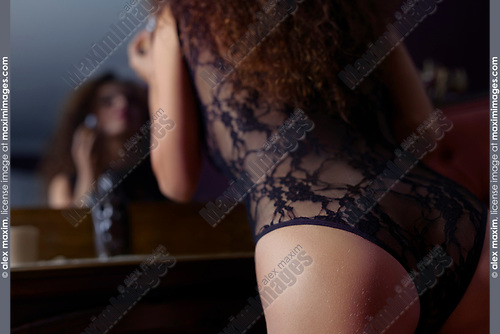 Artistic sensual closeup of a young woman in sexy black lacy underwear leaning onto a dresser towards the mirror applying lipstick. French retro style boudoir.