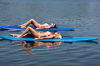 Two attractive, sexy Stand up paddle boarders suntan on Lady Bird Town Lake.