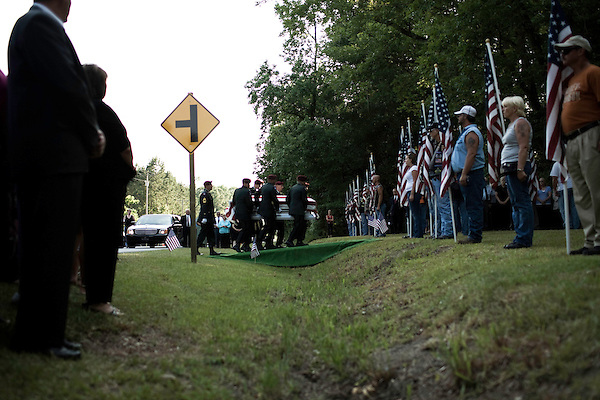 July 3, 2008. Pinetown, NC.. The funeral of Spc. Joel A. Taylor, assigned to the 1st Squadron, 3rd Armored Cavalry Regiment, Fort Hood, Texas; died June 25 in Mosul, Iraq, of wounds sustained when his vehicle encountered an improvised explosive device on June 24, 2008. He was 20.. Members of the Patriot Guard line the road next to the Taylor family cemetery as Spc. Taylor's casket is unloaded and taken to the funeral site.