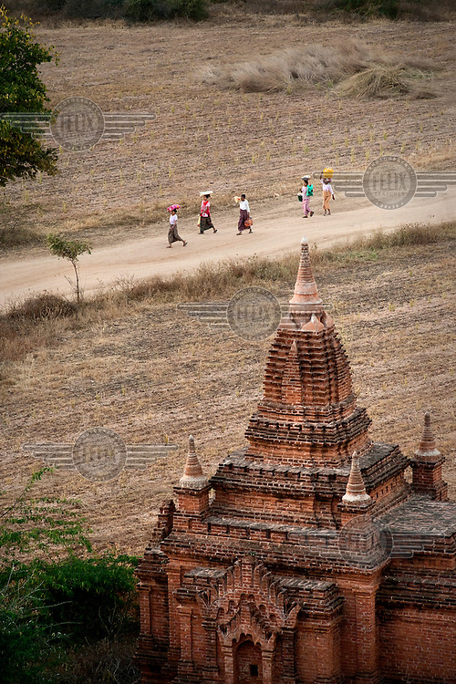 Viewed from a level on Shwesandaw pagoda, women walk carrying loads on their heads past a temple.