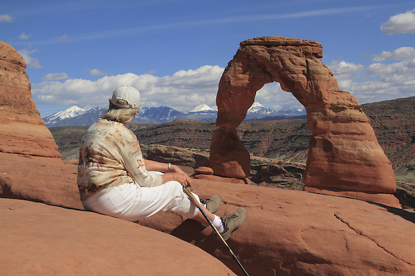 Mature woman sitting at Delicate Arch in Arches National Park, Moab, Utah, USA. .  John offers private photo tours in Arches National Park and throughout Utah and Colorado. Year-round.
