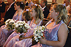 Group of bridesmaids sitting in church pew holding bouquets of flowers,