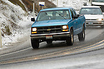 Blue Chevy driving in snow