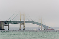 "A view of the Mackinac Bridge and its towers disappearing in the low clouds. The US Coast Guard cutter ""Mackinaw"" travels below the bridge. Mackinaw City, MI"