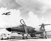 "On the flight line, United States Air Force technicians prepare a McDonald RF-101 Voodoo for a photo reconnaissance mission.  Overhead, a Fairchild C-123 Provider takes off on another assault airlift sortie, providing an air bridge to an outpost in South Vietnam.  High above, a Cessna O-1E ""Bird Dog"" returns after pointing out Viet Cong targets to pilots of strike aircraft on January 6, 1967..Credit: U.S. Air Force via CNP"
