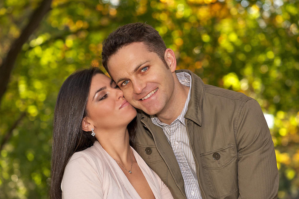 Affectionate engagement portrait of couple in Riverside Park.