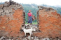 A girl stands in front of her destroyed house near at Malanchi, outskirt of Kathmandu, Nepal. May 11, 2015