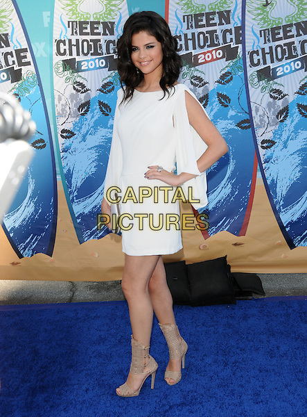 SELENA GOMEZ .Arrivals - Fox Teen Choice 2010 Awards held at Universal Ampitheatre in Universal City, California, USA,.August 8th 2010..full length white dress hand on hip  slit silver ring beige gladiator sandals open toe clutch bag long sleeve .CAP/RKE/DVS.©DVS/RockinExposures/Capital Pictures.
