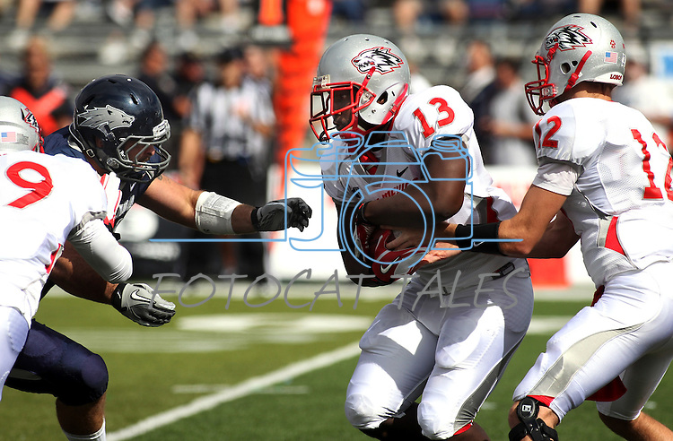 Nevada defender Jack Reynoso reaches in as New Mexico quarterback B.R. Holbrook hands off to James Wright during an NCAA football game in Reno, Nev., on Saturday, Oct. 15, 2011. (AP Photo/Cathleen Allison)