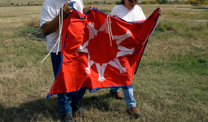 Emerson and Gerilyn Elk from Wounded Knee holding a Lakota flag. Emerson and Gerilyn sell art and handmade dream catchers near the famous cemetery to visiting tourists.