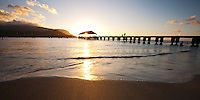 The sun sets through historic Hanalei Pier, Hanalei Bay, Kauai