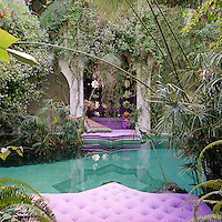 Pink star-shaped mattresses provide seating around a natural pool in the central courtyard which is framed with papyrus and rose geraniums